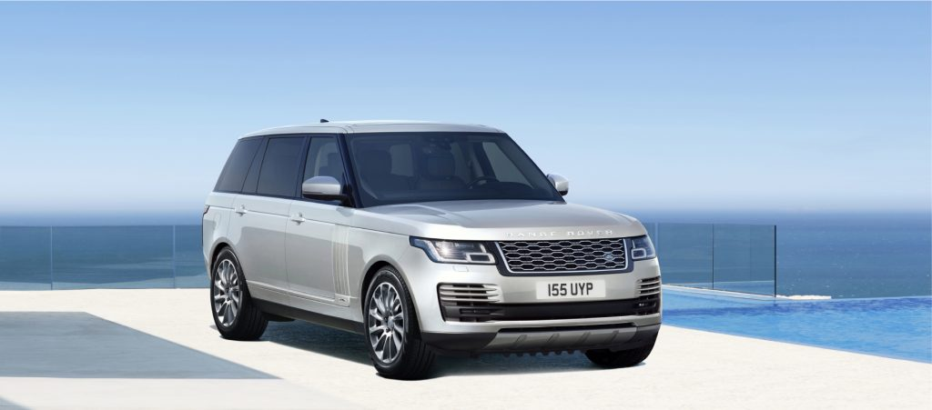 A silver 2021 Range Rover on display with a blue sky background