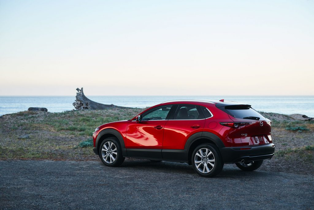 A red 2021 Mazda CX-30 parked near the ocean