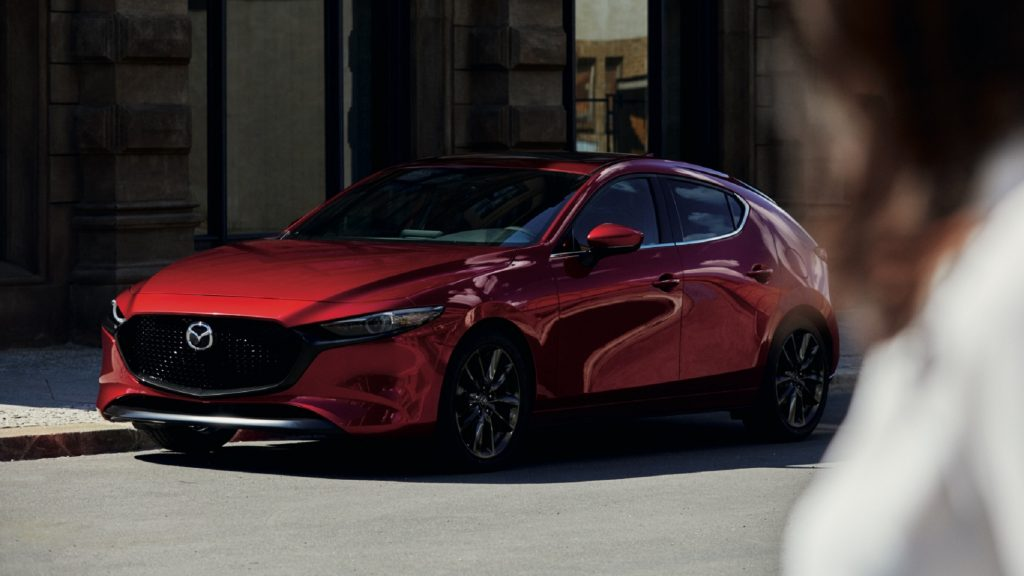 The front 3/4 view of a red 2021 Mazda3 Turbo Premium Plus on a city street
