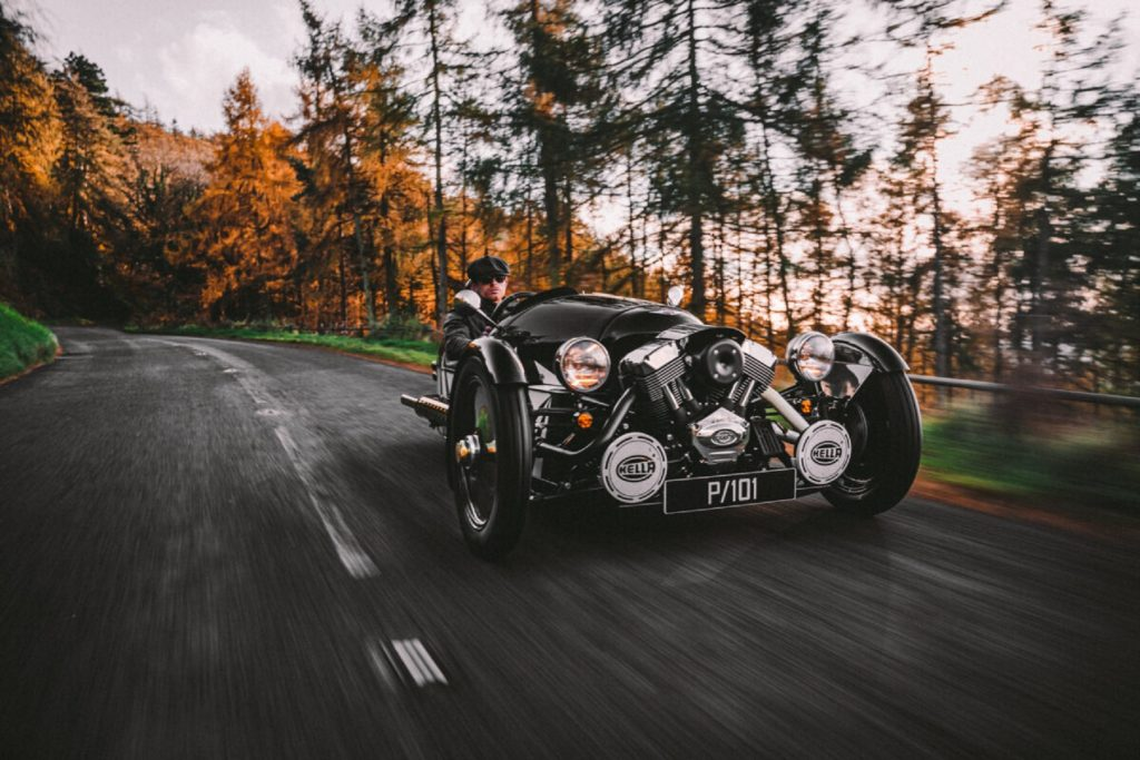 A black-and-white 2021 Morgan 3-Wheeler Belly Tank drives through a fall forest