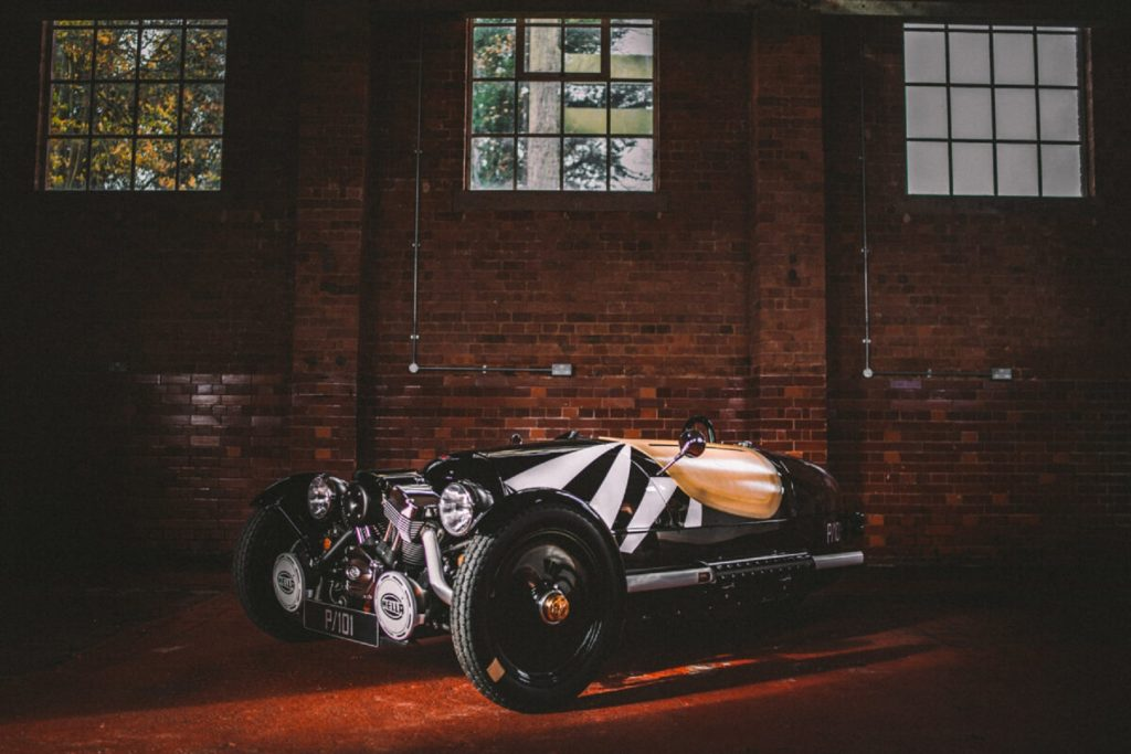 The front 3/4 view of a black-and-white 2021 Morgan 3-Wheeler Dazzleship P101 Edition with a tan cover in a red brick warehouse