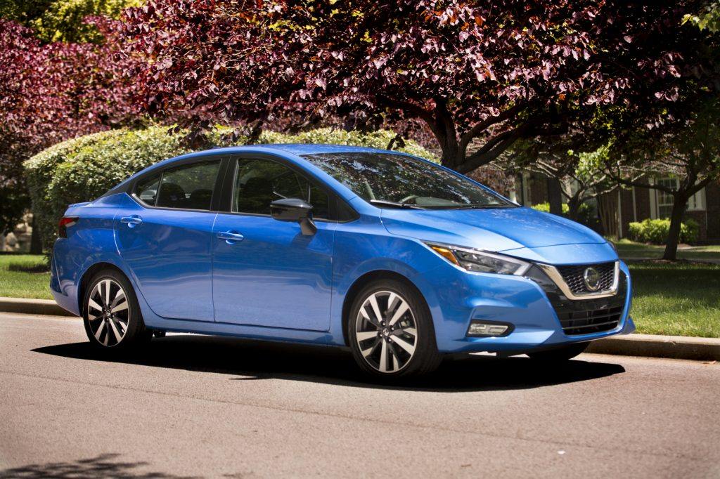 A blue 2021 Nissan Versa parked in front of some colorful trees
