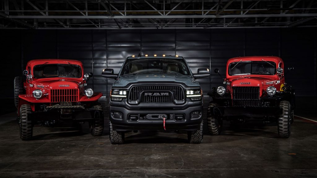 A gray 2021 Ram Power Wagon 75th Anniversary Edition flanked by a red 1946 Dodge Power Wagon and red Power Wagon Wrecker