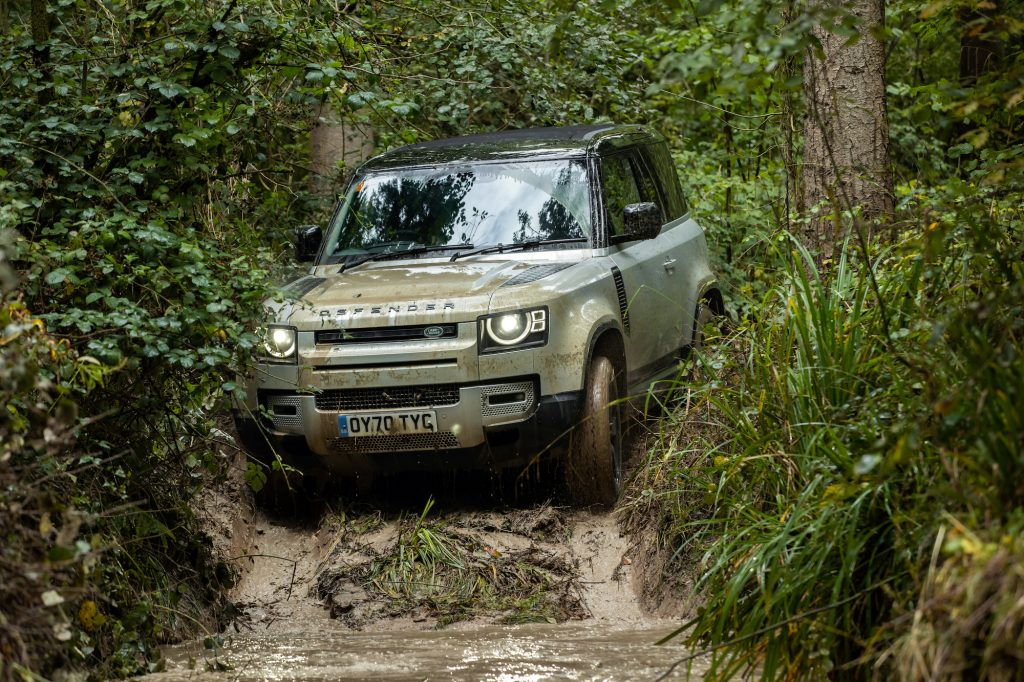 A 2021 Silver Land Rover Defender drives on rough terrain.