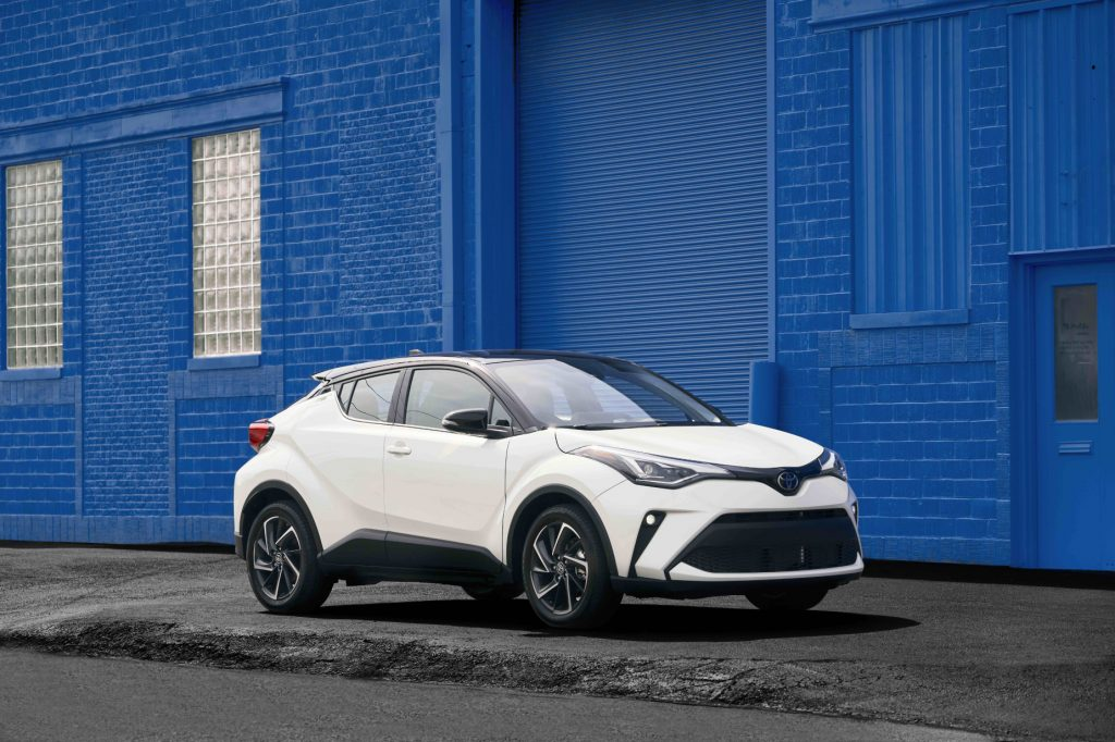 A white 2021 Toyota C-HR parked on display next to a blue wall