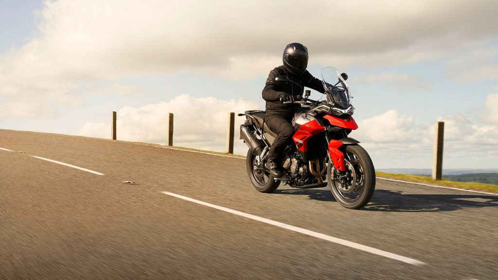 A rider on a red 2021 Triumph Tiger 850 Sport