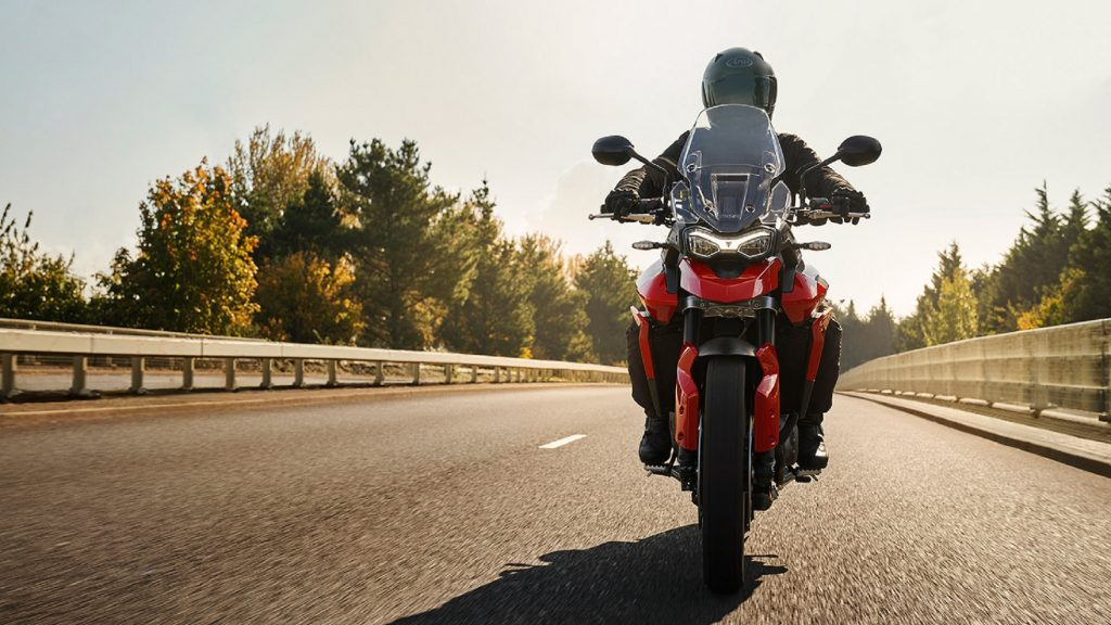 The front view of a rider on a red 2021 Triumph Tiger 850 Sport