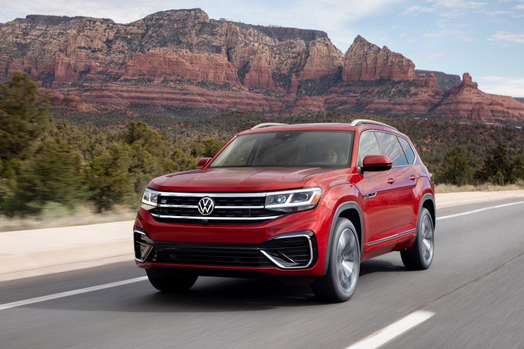 A red 2021 Volkswagen Atlas SEL Premium 4Motion on a paved road with mountains in the background.