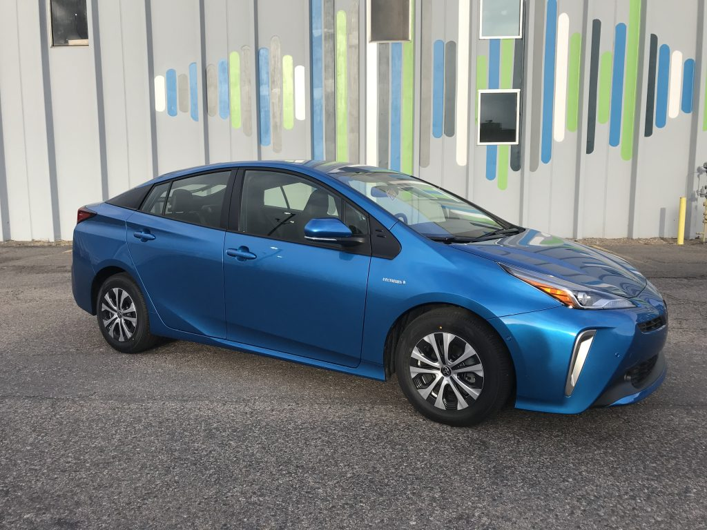An electric blue 2021 Toyota Prius parked on the street.