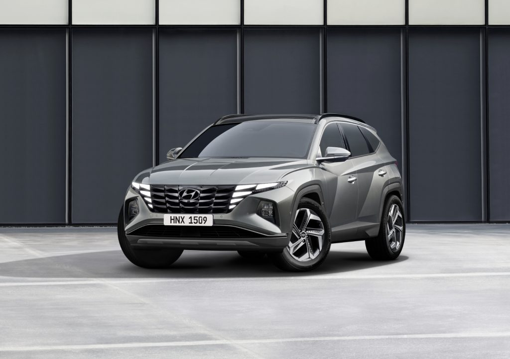 A grey 2022 Hyundai Tucson parked in front of a wall on display