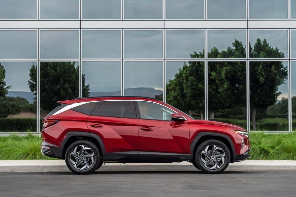 A red 2022 Hyundai Tucson parked in front a building with glass windows
