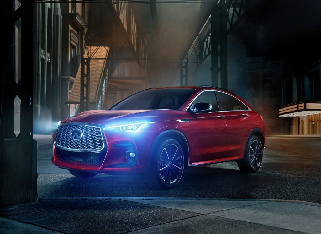 A red 2022 Infiniti QX55 parked on display in a dark alley