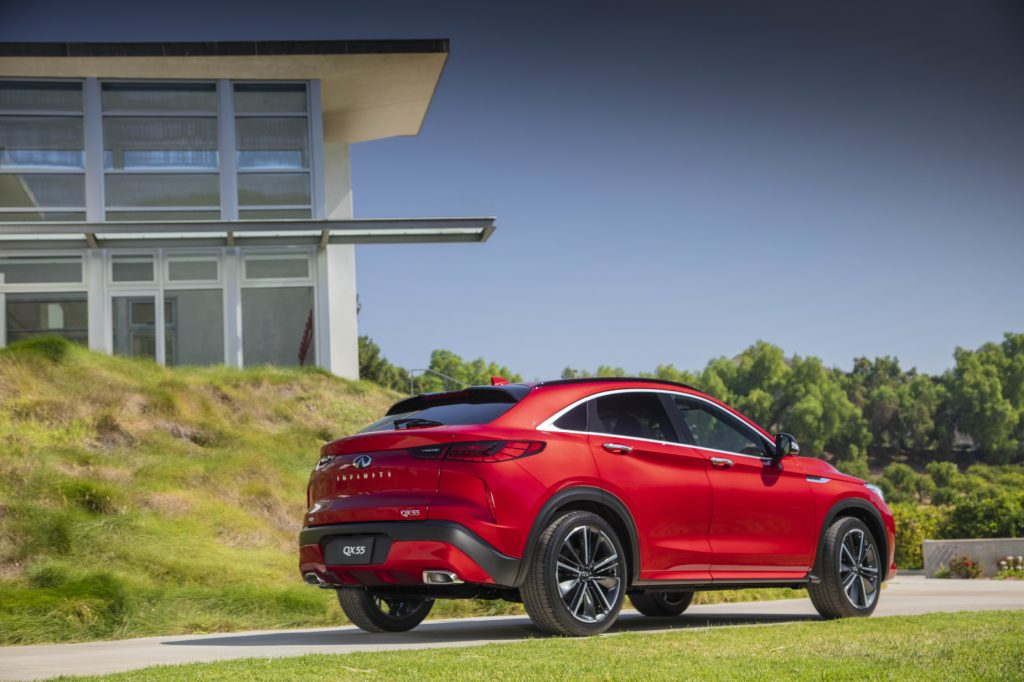 A red 2022 Infiniti QX55 driving away from a building