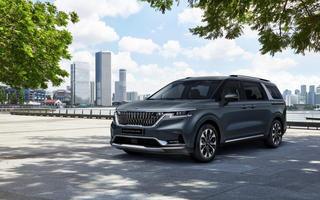 The 2022 Kia Sedona, aka 2022 Kia Carnival, parked on display with a cityscape in the background