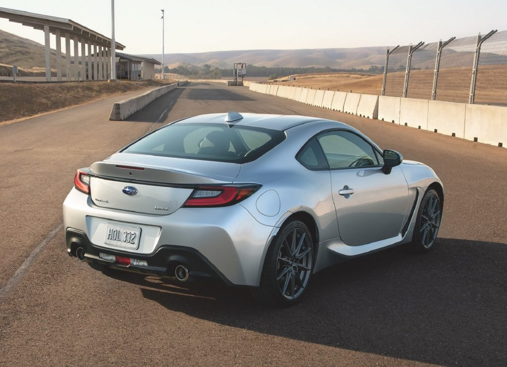 The rear 3/4 view of a silver 2022 Subaru BRZ on a racetrack