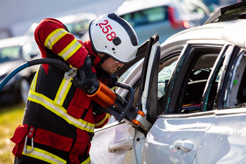 A safety training crew member uses the jaws of life on a Volvo.