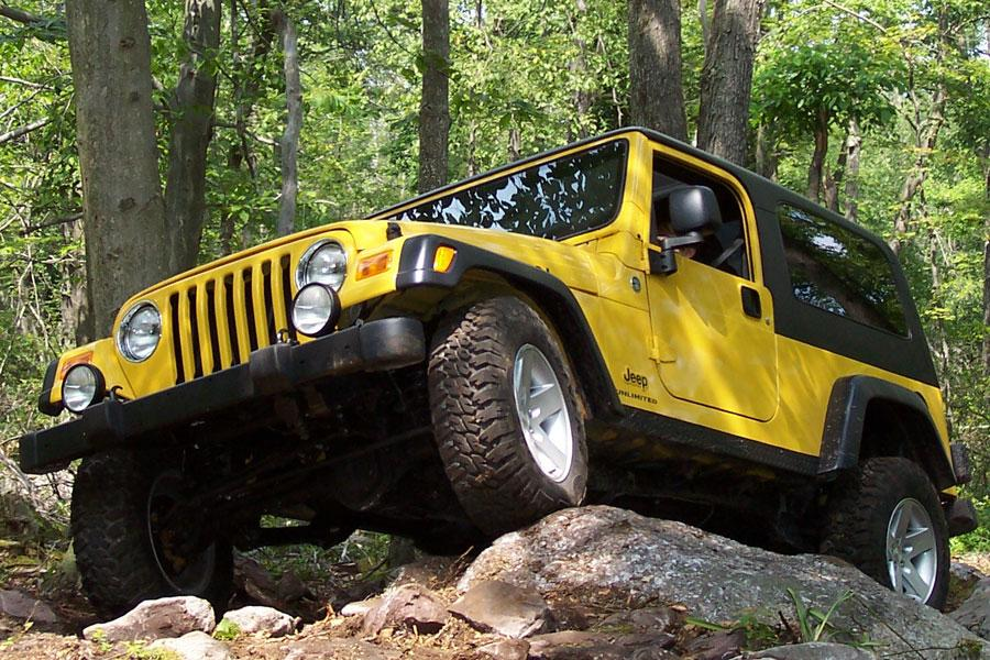 a yellow 2006 wrangler going off-road in the forest