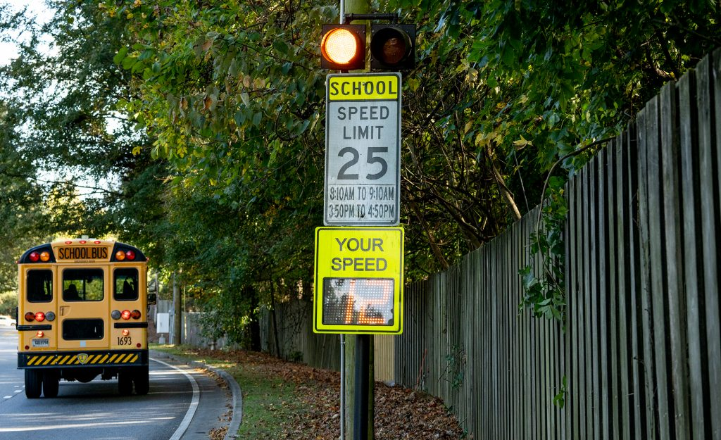 A school bus driving past a school zone safety beacon