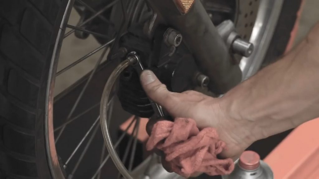 A mechanic bleeds a motorcycle's brakes