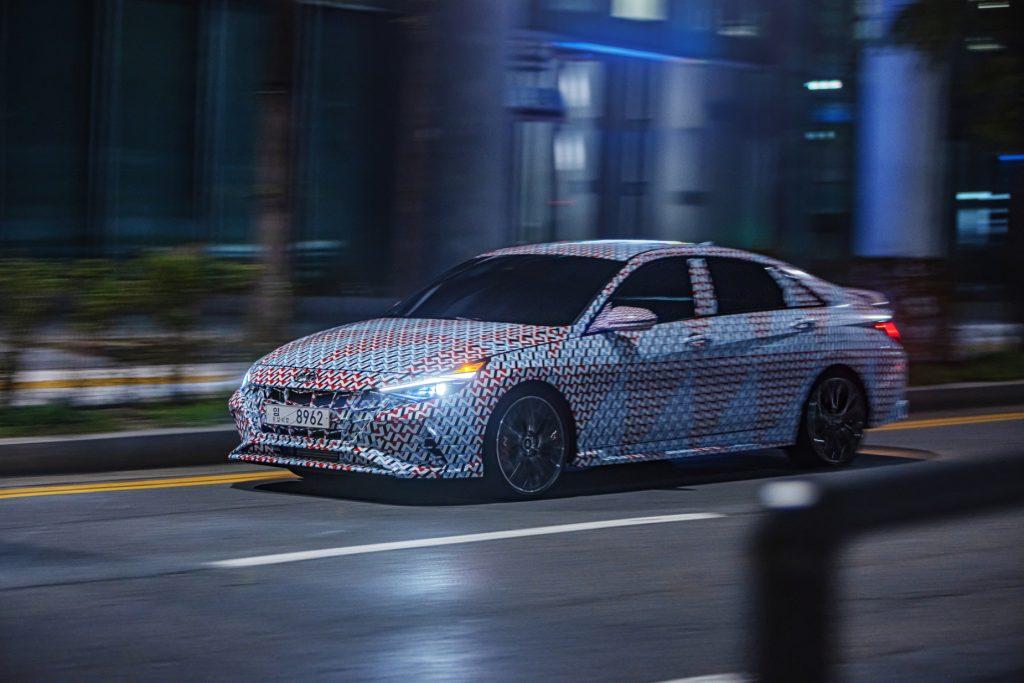 A camouflaged 2021 Hyundai Elantra N driving down a city street