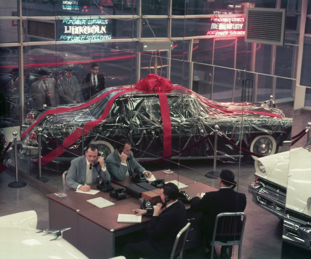 A car with a giant bow and gift wrap on display at a dealership