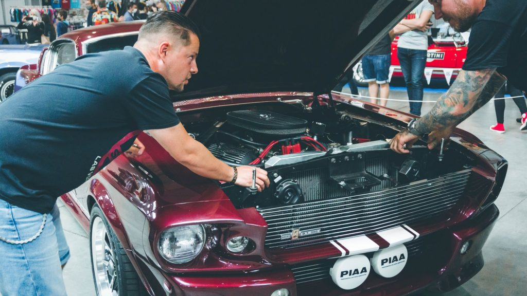 Two mechanic inspecting an engine of a red classic car.