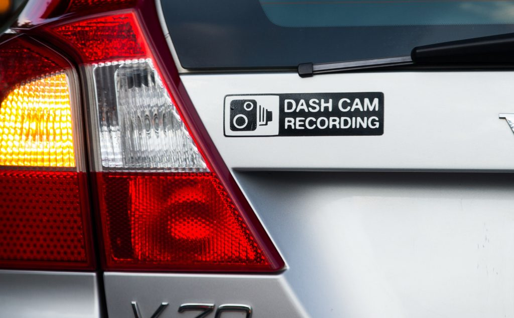 """Dashcam Recording"" is written on the sticker stuck to a car"