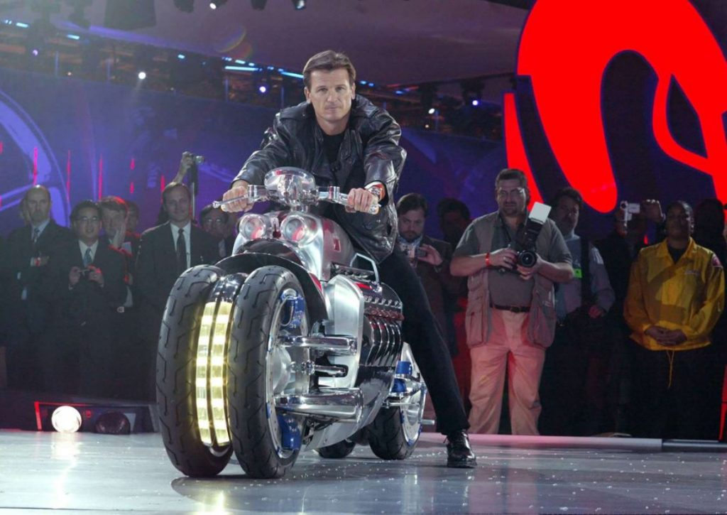 A rider brings in a large motorcycle to the 2003 North American International Auto Show. It has a Viper V10 engine.