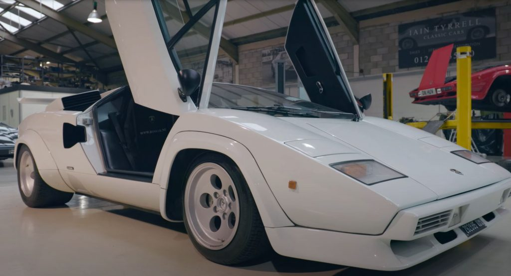 A white Lamborghini Countach sits in a shop with its doors swung up.