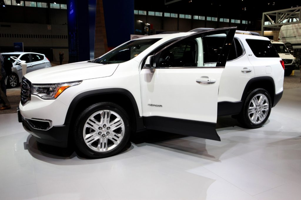 A white GMC Acadia on display at an auto show