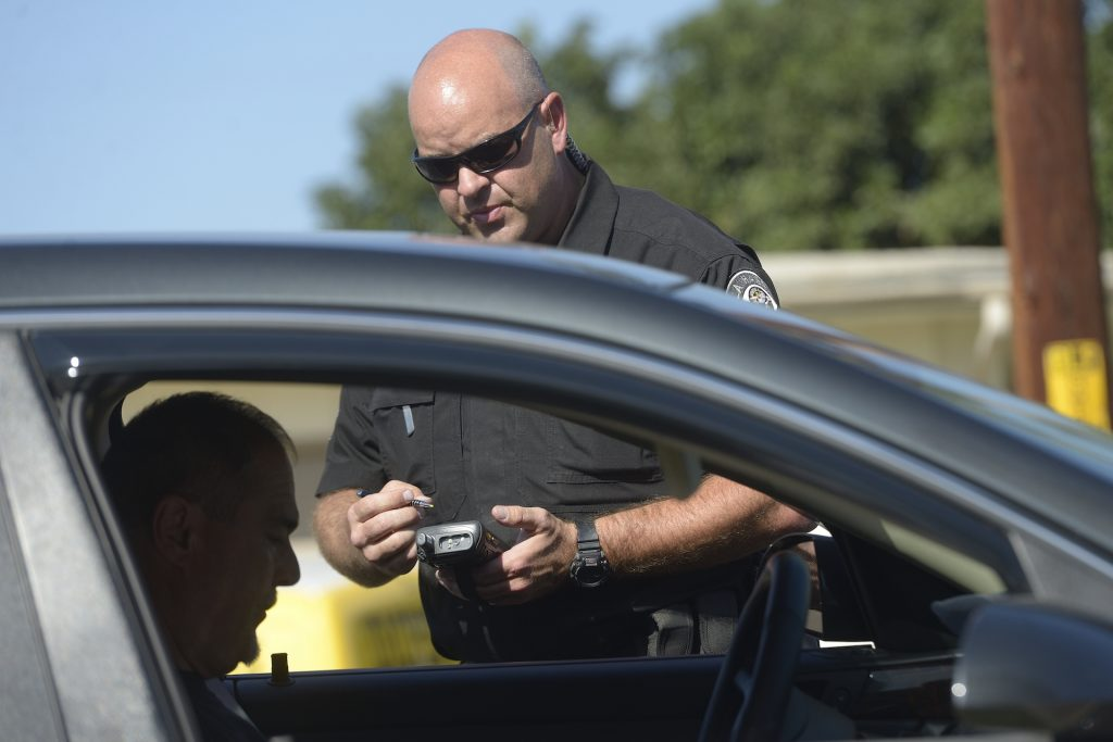 An image of a police officer handing out a speeding ticket.
