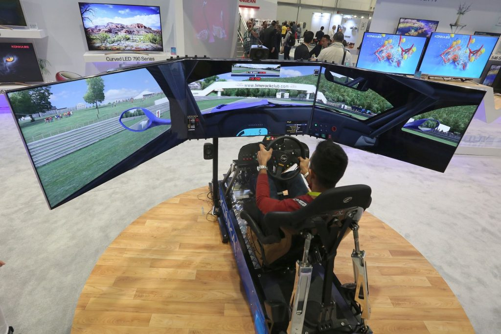 An image of someone playing a racing game with a simulator.