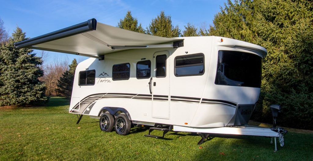 A white 2021 Terra Oasis travel trailer RV has the awning extended.