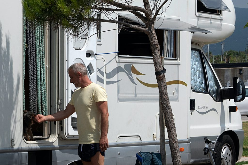 A man pets his dog inside a motorhome RV in a public parking in Castellon