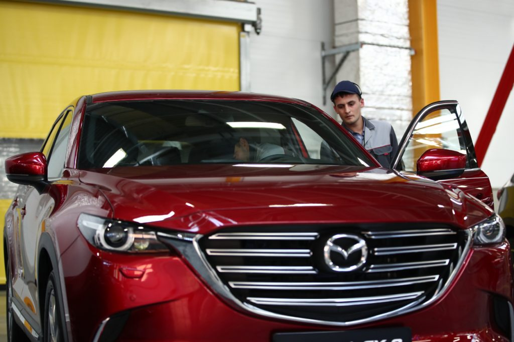 A man inspects a red Mazda CX-5