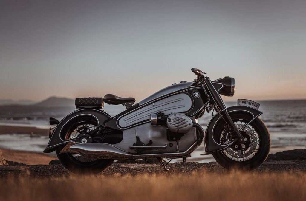 A black and white custom, hand made motorcycle against a backdrop of dusk.