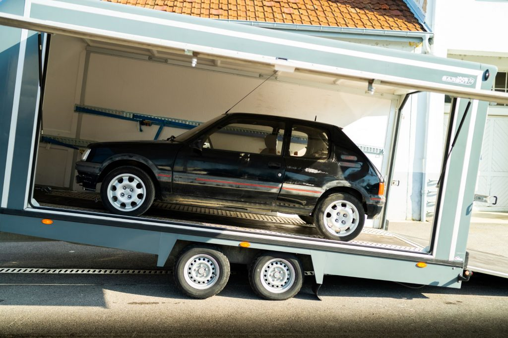 A black pre-restoration Peugeot 205 GTI in a trailer