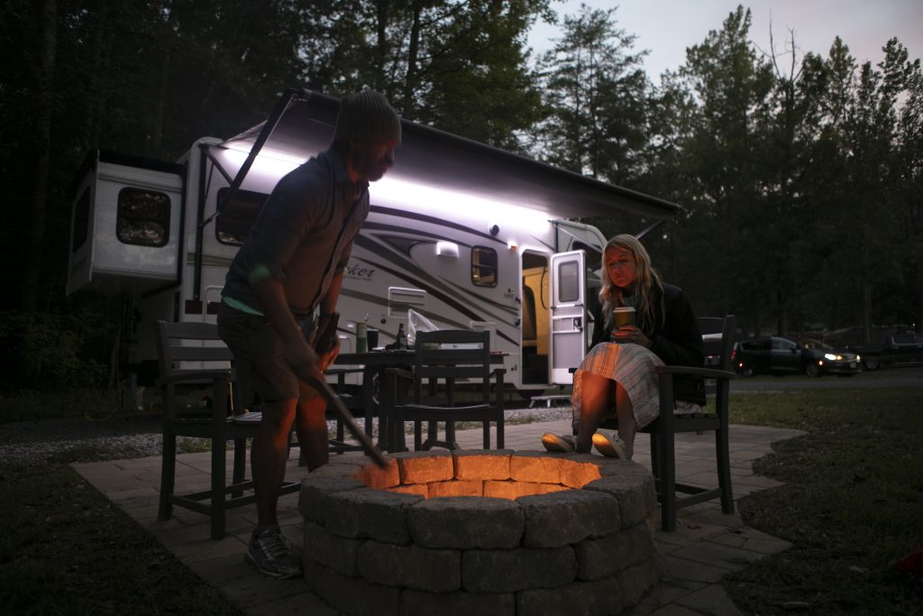 Christian Arriola and Washington Post travel writer Andrea Sachs sit around a fire outside of their rented RV Saturday, September 19, 2020 at a KOA campground