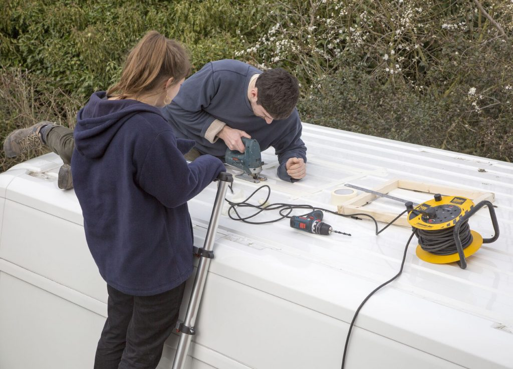 Cutting through roof of white metal camper van conversion to install ventilation window