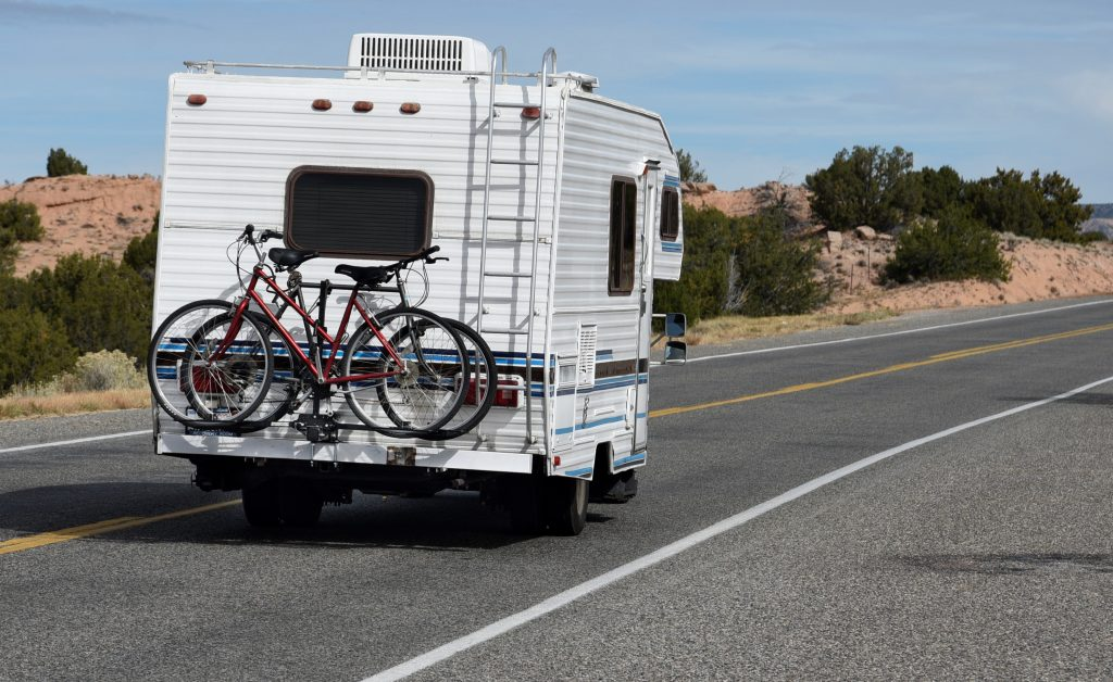 A tourist in an RV with bicycle racks approaches the small town of Chimayo, New Mexico