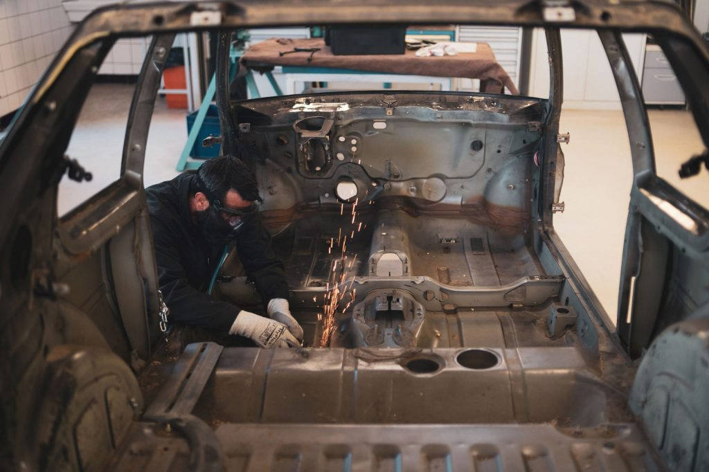 A restorer works on the bare-metal body of a Peugeot 205 GTI