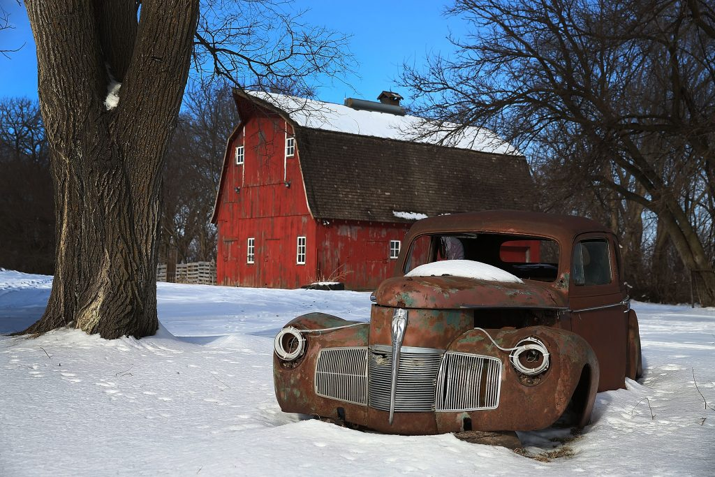 A rusty car in front of a barn in Iowa