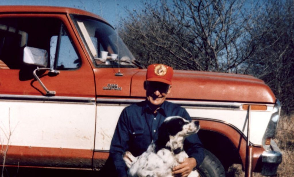 Sam Walton kneels in front of his red and white pickup to hug his dogs.