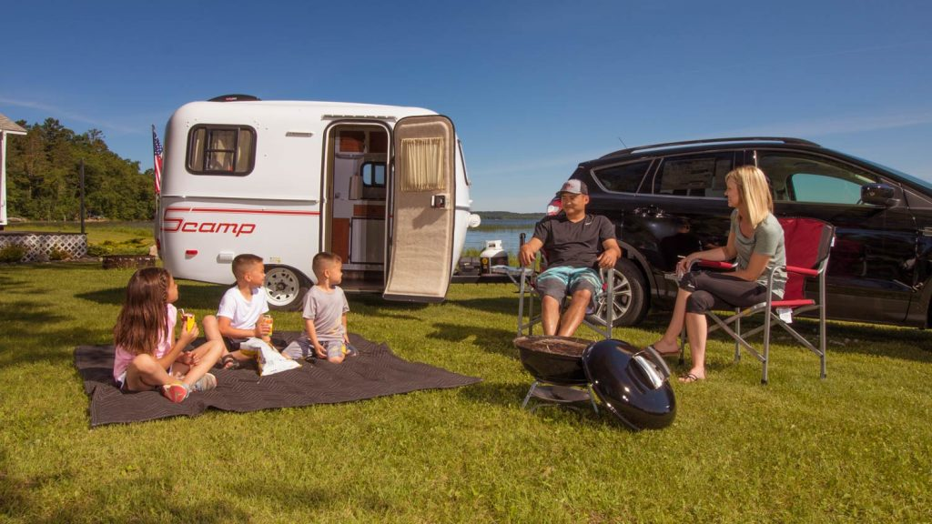 A family sitting outside in front of a Samp 13' Trailer.