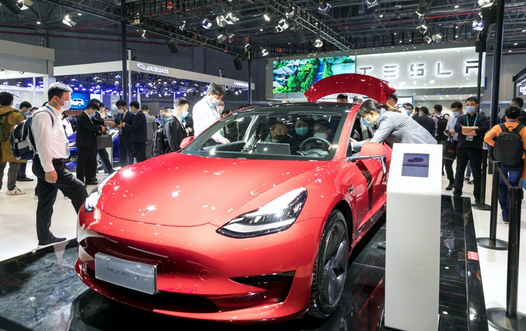 People view a Tesla Model 3 electric car at the auto exhibition area of the third International Import Expo