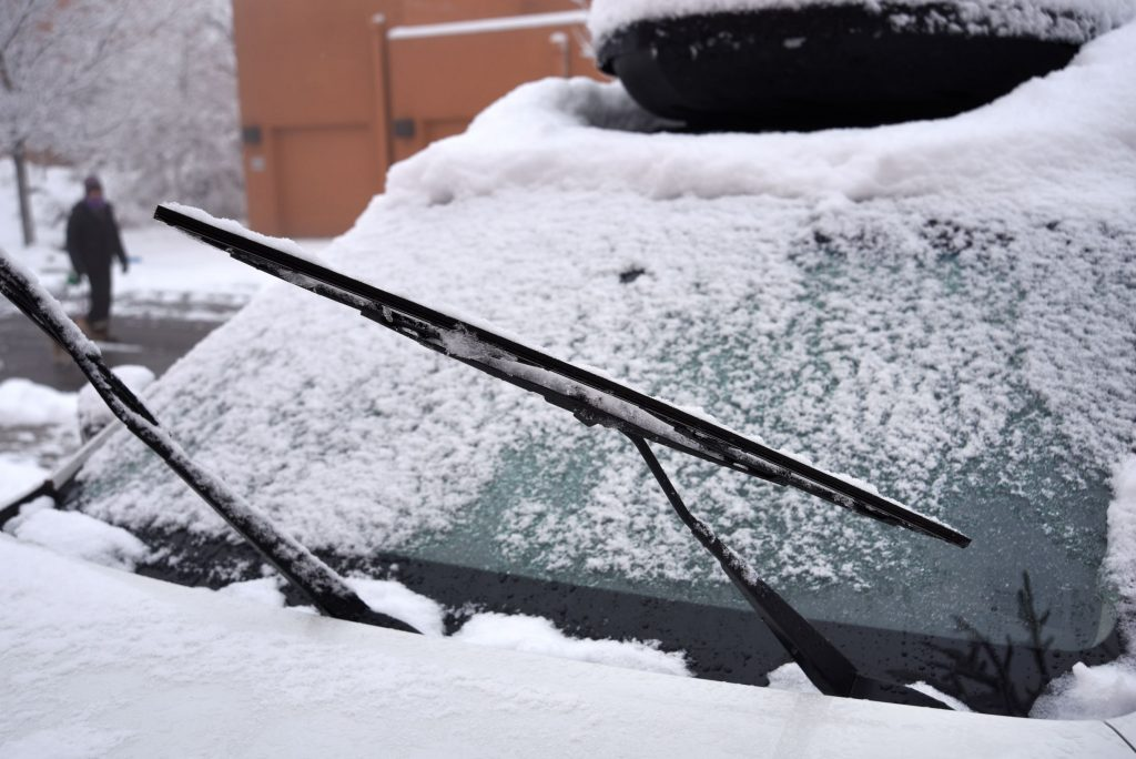 The windshield wipers and wiper blades of a snow-covered car