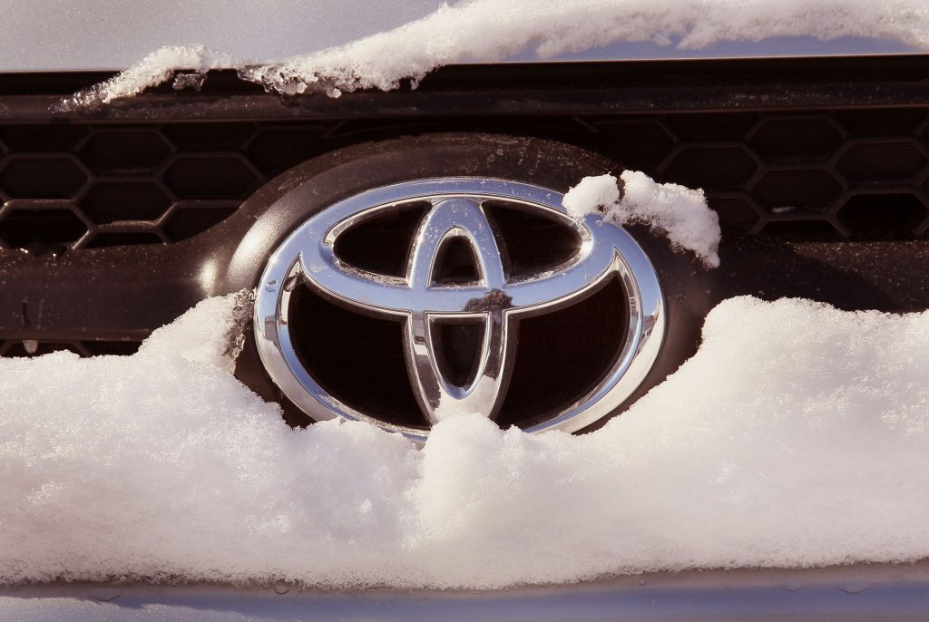 A Toyota logo seen on a snow covered SUV