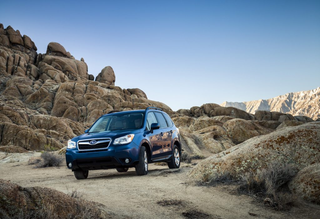 A Subaru Forester crossover SUV driving down a dirt road