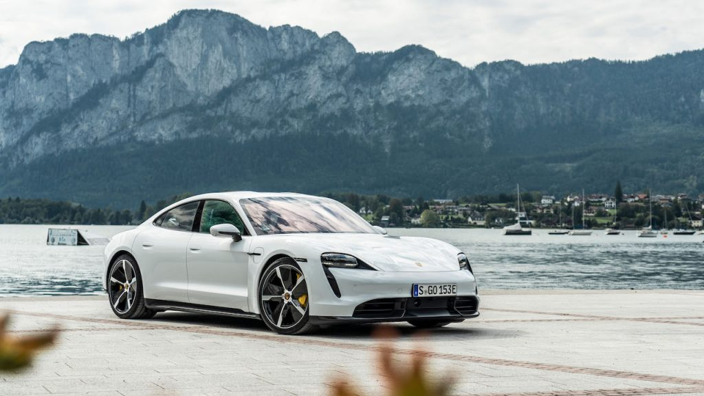 A photo of the Porsche Taycan outdoors by a lake.