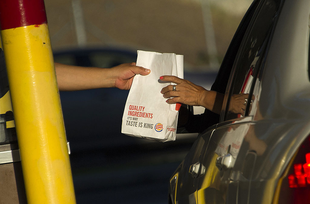 A worker hands food to a customer in a car at a Burger King restaurant.